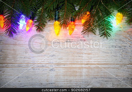 Christmas background with lights on branches stock photo, Multicolored Christmas lights on spruce branch with wooden background by Elena Elisseeva