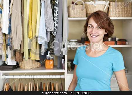 Smiling woman near closet stock photo, Happy woman standing in front of custom organized closet at home by Elena Elisseeva