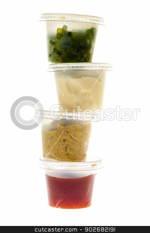 Stack of condiment containers stock photo, Relish mustard ketchup and mayonnaise condiments in clear containers stacked on white background by Elena Elisseeva