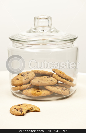 Chocolate chip cookies in jar stock photo, Glass cookie jar with chocolate chip cookies by Elena Elisseeva