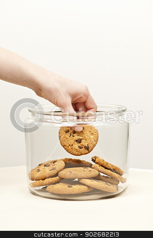 Stealing cookies from the cookie jar stock photo, Hand taking chocolate chip cookie from glass jar by Elena Elisseeva