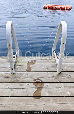 Footprints on dock at summer lake stock photo, Wet footprints on dock with ladder and diving platform at calm summer lake in Ontario Canada by Elena Elisseeva