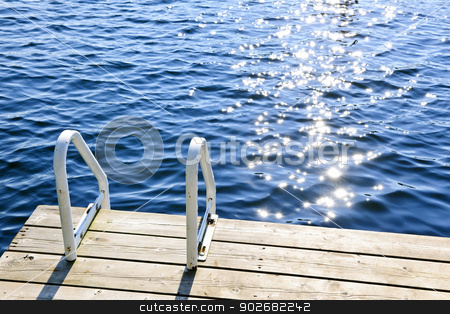 Dock on summer lake with sparkling water stock photo, Dock and ladder on calm summer lake with sparkling water in Ontario Canada by Elena Elisseeva