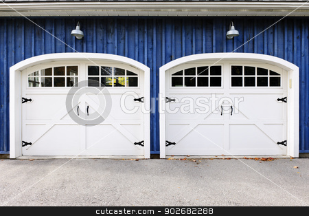 Double garage doors stock photo, Two white garage doors with windows on blue house by Elena Elisseeva