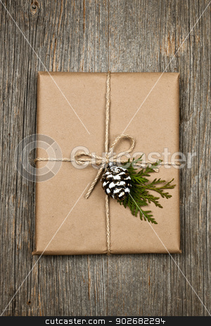 Christmas present in brown paper tied with string stock photo, Christmas gift in brown wrapping and string with pine cone decoration on old wood background by Elena Elisseeva