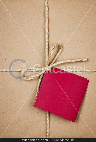 Gift with red tag in brown paper stock photo, Gift package and red card in brown paper wrapper tied with string close up by Elena Elisseeva