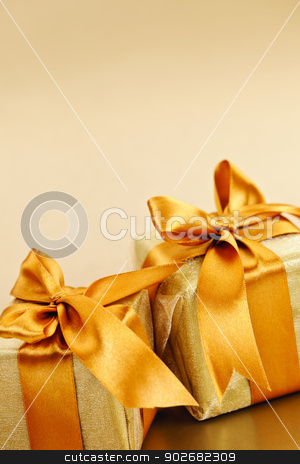 Two golden wrapped gift boxes stock photo, Two gift boxes wrapped in gold ribbons with copy space by Elena Elisseeva