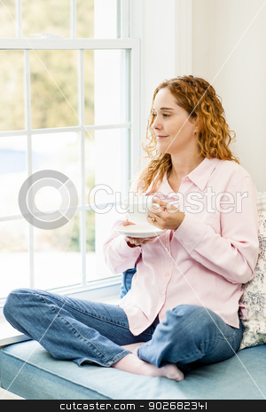 Woman relaxing by the window with coffee stock photo, Smiling caucasian woman relaxing on couch by window holding cup of coffee by Elena Elisseeva