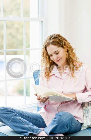 Woman reading book by window stock photo, Smiling caucasian woman reading book by window at home by Elena Elisseeva