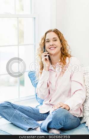 Woman talking on phone stock photo, Smiling caucasian woman talking on cordless telephone at home by Elena Elisseeva
