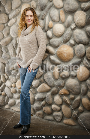 Woman in front of stone wall stock photo, Smiling woman standing in front of stone wall bull body by Elena Elisseeva
