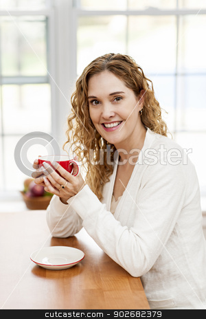 Smiling woman holding red coffee cup stock photo, Portrait of smiling woman holding red coffee cup sitting at table in home kitchen by window by Elena Elisseeva