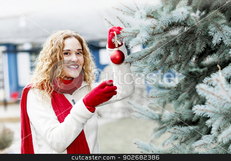Woman decorating Christmas tree outside stock photo, Joyful woman hanging Christmas ornaments on spruce tree outdoors in yard near home by Elena Elisseeva