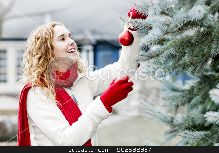 Woman decorating Christmas tree outside stock photo, Portrait of smiling woman hanging Christmas ornaments on spruce tree outdoors in yard near home by Elena Elisseeva
