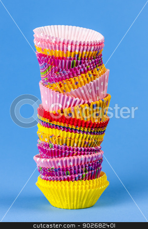 Muffin or cupcake baking cups stock photo, Tall stack of colorful muffin or cupcake cups on blue background by Elena Elisseeva