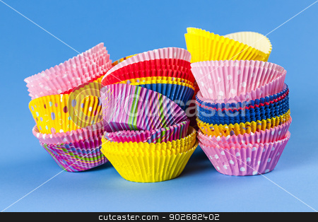 Muffin or cupcake baking cups stock photo, Several stacks of colorful muffin or cupcake cups on blue background by Elena Elisseeva