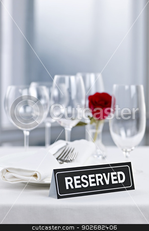 Romantic dinner setting with reserved sign stock photo, Reserved romantic table setting with roses plates and cutlery by Elena Elisseeva