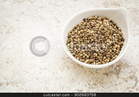 dry hemp seeds stock photo, small ceramic bowl of  dry hemp seeds against a ceramic tile background with a copy space by Marek Uliasz