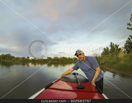 launching stand up paddleboard stock photo, mature male paddler launching a stand up paddleboard (SUP) on a lake in Colorado, summer by Marek Uliasz