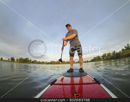 stand up paddling stock photo, mature male paddler enjoying workout on stand up paddleboard (SUP), calm lake in Colorado, summer by Marek Uliasz