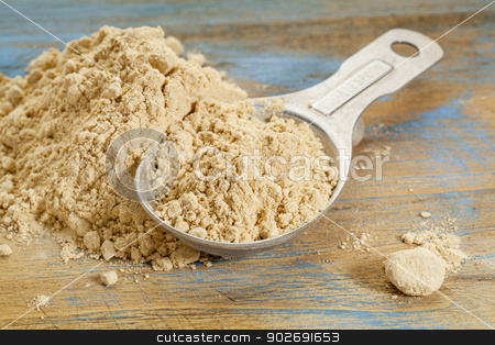 maca root powder stock photo, maca root powder - a measuring tablespoon and pile on wooden surface by Marek Uliasz