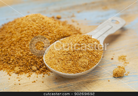 coconut palm sugar stock photo, unrefiined coconut palm sugar - measuring tablespoon and pile on wood surface by Marek Uliasz