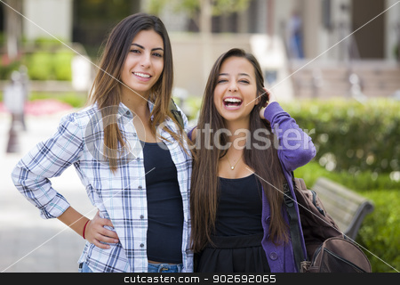 Mixed Race Female Students Carrying Backpacks on School Campus stock photo, Portrait of Two Attractive Mixed Race Female Students Carrying Backpack on School Campus. by Andy Dean