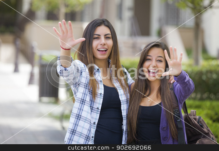 Mixed Race Female Students Waving Carrying Backpacks on School C stock photo, Portrait of Two Attractive Mixed Race Female Students Waving and Carrying Backpacks on School Campus. by Andy Dean