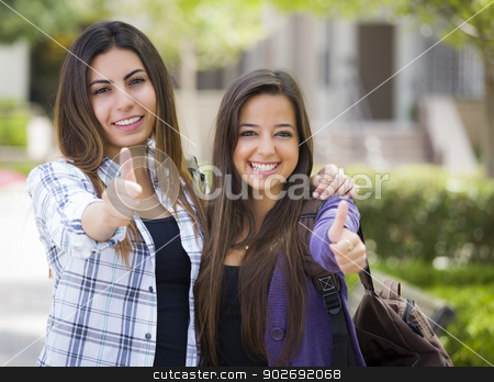 Mixed Race Female Students on School Campus With Thumbs Up  stock photo, Portrait of Two Attractive Mixed Race Female Students With Thumbs Up and Carrying Backpacks on School Campus. by Andy Dean