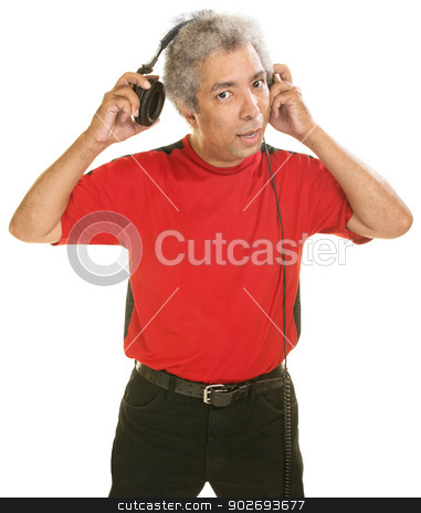 Man Removing Headphones stock photo, Middle aged Hispanic man removing large headphones by Scott Griessel