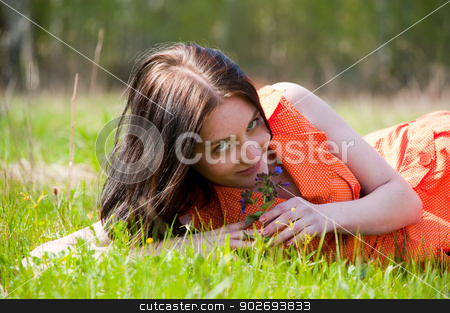 Pretty girl laying on grass stock photo, Young beautiful woman in orange dress laying on grass by Aikon