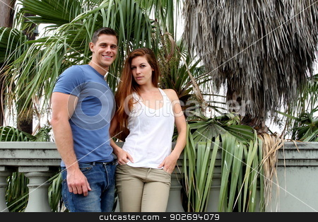 Young Couple Palm Tree stock photo, Young couple in front of a palm tree. by Henrik Lehnerer