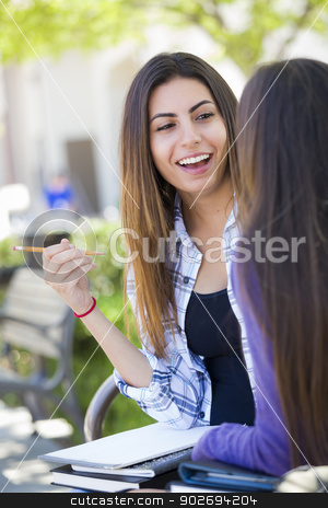 Expressive Young Mixed Race Female Sitting and Talking with Girl stock photo, Attractive Expressive Young Mixed Race Female Student Sitting and Talking with Girlfriend Outside on Bench. by Andy Dean