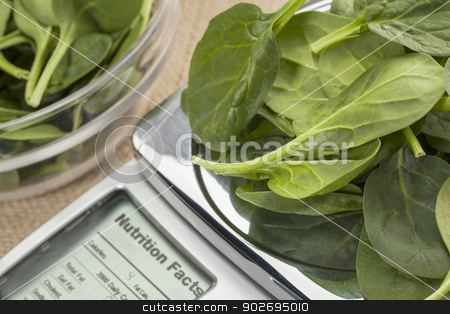 fresh spinach on diet scale stock photo, fresh spinach  on diet scale displaying nutrition facts - a diet concept by Marek Uliasz