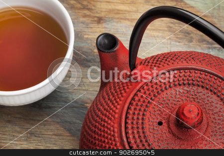 cup of tea with red tetsubin stock photo, red tetsubin with a cup of tea - a detail of a traditional cast iron Japenese teapot by Marek Uliasz