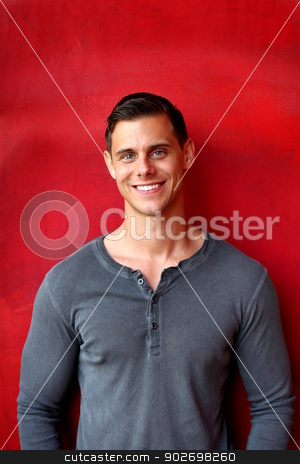 Portrait of a man stock photo, Portrait of a man with gray shirt in front red wall. by Henrik Lehnerer