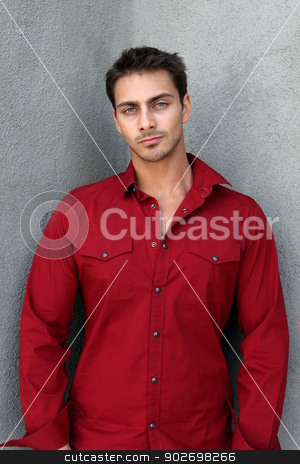 Portrait of a man stock photo, Portrait of a man with red shirt in fornt gray wall. by Henrik Lehnerer