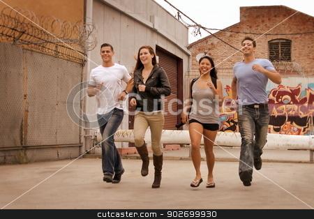 Group Running stock photo, Group of friends running in urban environment.  by Henrik Lehnerer