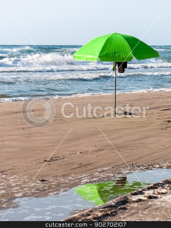 Green parasol with reflection stock photo, Green parasol with reflection in pool of water on a beach. by ArtesiaWells