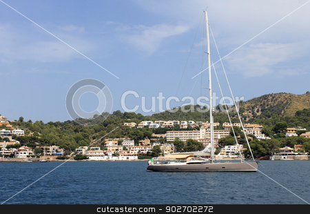Alcudia coastline stock photo, Scenic view of Alcudia coastline with yacht moored in foreground, Majorca, Spain. by Martin Crowdy