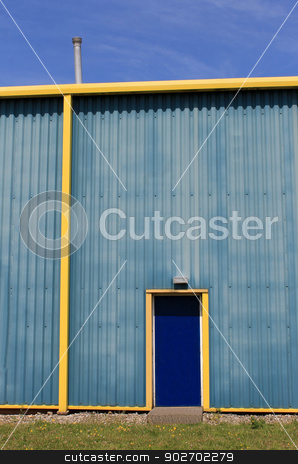 Blue and yellow warehouse building stock photo, Exterior of blue and yellow modern warehouse building, sky background. by Martin Crowdy