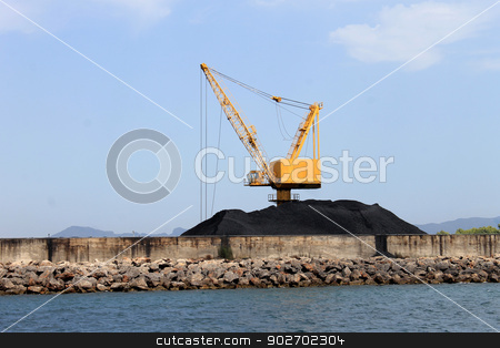 Crane and pile of coal on docks stock photo, Scenic view of yellow industrial crane and pile of coal on docks, Alcudia harbor, Majorca, Spain. by Martin Crowdy