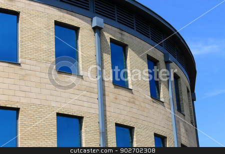 Curved modern office building stock photo, Exterior of curved modern office building with blue windows. by Martin Crowdy