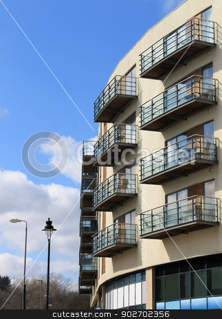 Modern apartment building stock photo, Exterior of modern apartment building with cloudscape background. by Martin Crowdy