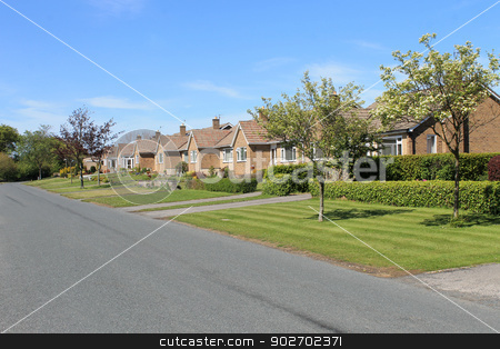 Row of bungalows in village stock photo, Row of bungalows in village with blue sky background. by Martin Crowdy