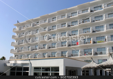 White Spanish hotel building stock photo, White Spanish hotel building with parasols in foreground. by Martin Crowdy