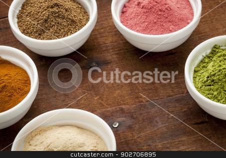 super fruit and leaf powders stock photo, super fruit and leaf powders in small ceramic bowls with copy space - baobab, nori, yumberry, moringa, mangosteen by Marek Uliasz