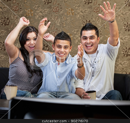 Latino Family Celebrating stock photo, Latino family of three celebrating in front of television by Scott Griessel