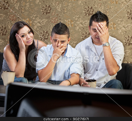 Cringing Family at Television stock photo, Disappointed Hispanic family sitting in front of television by Scott Griessel