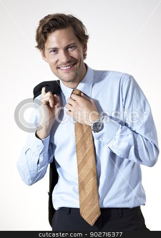 Smiling businessman casual looking stock photo, Smiling casual businessman correcting his tie by Thomas Rugdal